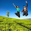 Jumping couple in green field. Stock Photography
