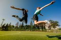 Jumping couple in sunny green field Stock Photo