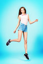 Jumping easy beautiful girl teenager wearing casual clothes posing at studio full length Royalty Free Stock Photo