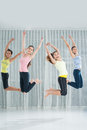 Jumping exercises young women in the aerobics class smiling and looking at camera Royalty Free Stock Images