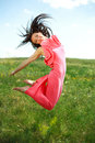 Jumping and flying graceful girl on the background of blue sky clouds Stock Image