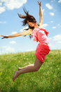 Jumping and flying graceful girl on the background of blue sky clouds Stock Photo