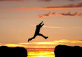 Jumping a gap in sunset silhouetted man Royalty Free Stock Photos