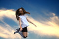 Jumping girl teeny with striped socks against the sky Royalty Free Stock Images