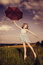 Jumping girl with umbrella teen an in front of rural landscape Stock Image