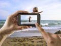Jumping for joy man taking a picture with your mobile phone a one woman on the beach Royalty Free Stock Images