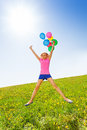Jumping positive girl with balloons in summer flying the air Royalty Free Stock Photography