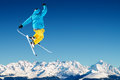 Jumping skier in high mountains at jump Royalty Free Stock Images