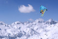 Jumping skier at jump inhigh mountains at sunny day Stock Photography