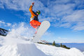 Jumping snowboarder from hill in winter Royalty Free Stock Photo