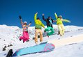 Jumping snowboarders four friends in bright vivid clothes in snow with mountains on background Stock Photography