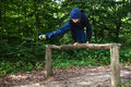 Jumping a teenage boy is across a hurdle in a forest Royalty Free Stock Photography