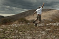 Jumping trekker a young adult and exulting on a mountain background Stock Photo