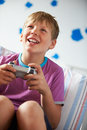 Junge der kontrolleur playing video game hält Stockbild