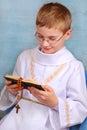 Junge der zur ersten heiligen kommunion mit gebetsbuch geht Stockbild