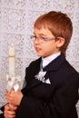 Junge mit Kerze am Tag der ersten heiligen Kommunion Stockfotos