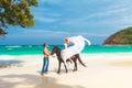 Junge paare in der liebe die mit dem pferd auf einem tropischen strand geht Lizenzfreie Stockfotos