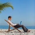 Junger geschäftsmann auf seinem strandstuhl unter verwendung seines laptops Lizenzfreie Stockfotografie