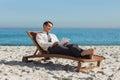 Junger geschäftsmann der auf einem klappstuhl unter verwendung seiner tablette sich entspannt Lizenzfreie Stockfotos