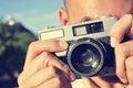 Junger mann der ein foto mit einer alten kamera macht Stockbild