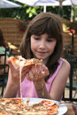 Junges Mädchen, das Pizza isst Stockbilder