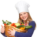 Junior cook holding a basket with vegetables Stock Image