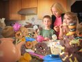 Junk food snack kids getting caught by mom two children are eating messy snacks such as cookies donuts and cupcakes in the kitchen Royalty Free Stock Photo