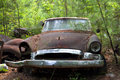 Junk yard car in trees and weeds Stock Images