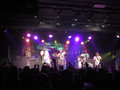 Jurassic 5 singers raps and DJ spin on stage as fans cheer