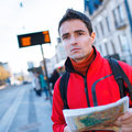 Just arrived: handsome young man studying a map on a bus stop Royalty Free Stock Photo