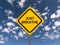 Just breathe sign with blue sky and clouds in the background conceptual image Royalty Free Stock Image