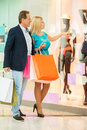 Just look at that full length of cheerful mature couple shopping in shopping mall while women pointing mannequin Royalty Free Stock Photos