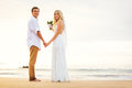 Just married couple holding hands on the beach hawaii wedding Stock Photo