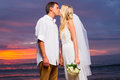 Just married couple kissing on tropical beach at sunset hawaii wedding Royalty Free Stock Photography