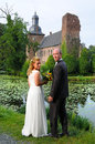 Just married couple posing in front of an old castle Royalty Free Stock Photography