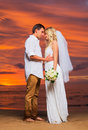 Just married couple on tropical beach at sunset intimate loving moment wedding Stock Photography