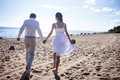Just married happy couple running on a sandy beach, view from the back Royalty Free Stock Photo