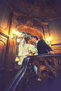 Just married kisses on the stairs in the hall of old theatre Royalty Free Stock Photo