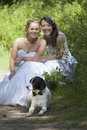 Just married lesbian pair with dog in forest white wedding dresses and their Stock Image