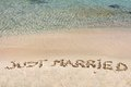 Just married written in sand on a beautiful beach blue clear waves background Stock Image