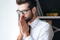 Just a moment to overthink everything handsome young businessman in glasses looking thoughtful and keeping hands clasped while Stock Photo