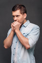 Just a moment to overthink everything side view of handsome young man keeping hands clasped and looking thoughtful while standing Royalty Free Stock Image