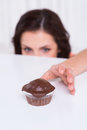 Just one more young woman looking out of the table and stretching hand to the chocolate muffin laying on the table Royalty Free Stock Image