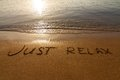 Just relax the inscription on sand near a sea edge Royalty Free Stock Image