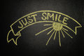 Just smile with Ribbon Banner, written with chalk on a blackboar Royalty Free Stock Photo