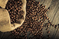 Jute bag with coffee beans close up of full of and some scattered on a wooden table Stock Photography