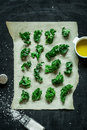 Kale bits on baking paper preparing kale chips kitchen scenery captured from above top view healthy dietetic snack with salt and Royalty Free Stock Photos
