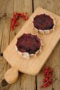 Kalitki russian rye cakes with berry filling on a wooden board and red currants wood background Royalty Free Stock Photos