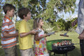 Kantjusterad fader serving grilled food till ungar utomhus Royaltyfri Bild