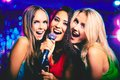 In karaoke bar portrait of happy girls singing microphone the Stock Photo